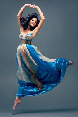 Cuadro hermosa niña flotando en el aire, vestido de seda azul