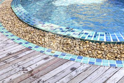 Hermosa piscina decorada por adoquines redondos para el for Drenaje de piscina