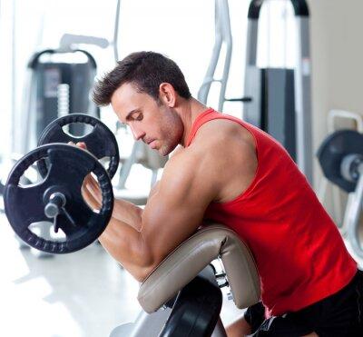 Cuadro hombre con el equipo de entrenamiento con pesas en el gimnasio de deporte