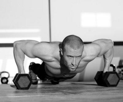 Cuadro Hombre de la gimnasia plancha fuerza de flexión de brazos con mancuernas