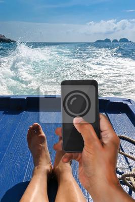 Hombre el día de fiesta con el teléfono inteligente en un barco en movimiento entre la isla