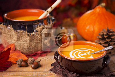 Homemade pumpkin soup on a rustic table with autumn decorations