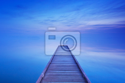 Jetty on a still lake at dawn in The Netherlands