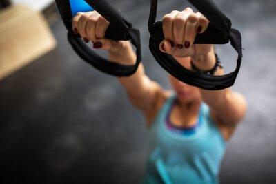 Cuadro Joven mujer en el gimnasio trabajando en su abs en trx
