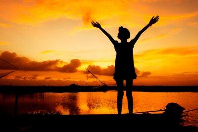 Cuadro Juego de niña linda en el fondo de la puesta de sol río