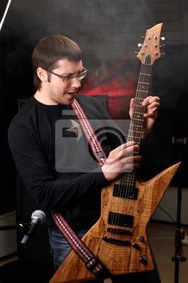 juego masculino joven en estudio en la guitarra