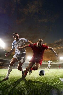Cuadro Jugadores de fútbol en la acción en el estadio del atardecer de fondo