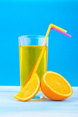 Cuadro Jugo de naranja en un vaso con pajas de colores y rodajas de naranja sobre un fondo azul