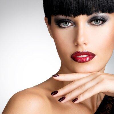 Cuadro La cara de una mujer con las uñas hermosas oscuros y labios rojos atractivos