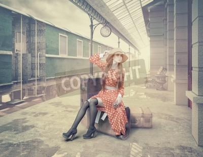 Cuadro La muchacha que se sienta en la maleta que espera en la estación de tren retra. Estilo de tarjetas de color vintage