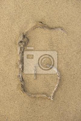 Letra G del alfabeto hecha de trozos de madera sobre la arena