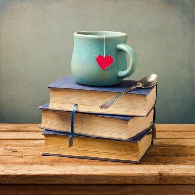 Cuadro Libros antiguos viejos y una taza con forma de corazón en la mesa de madera