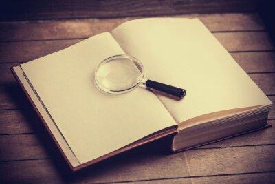 Cuadro Loupa y libro sobre la mesa de madera