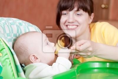 Madre de alimentación bebé con una cuchara