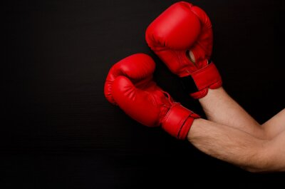 Cuadro Mano en guantes de boxeo rojos en la esquina del marco sobre un fondo negro, espacio vacío