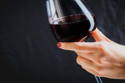 Cuadro Mano sosteniendo el vaso de vino tinto sobre fondo gris oscuro