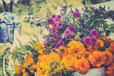 Cuadro Manojo de flores en una silla blanca. Bicicleta borrosa retro en el bac