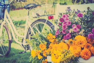 Cuadro Manojo de flores en una silla blanca. Bicicleta borrosa retro en el fondo.