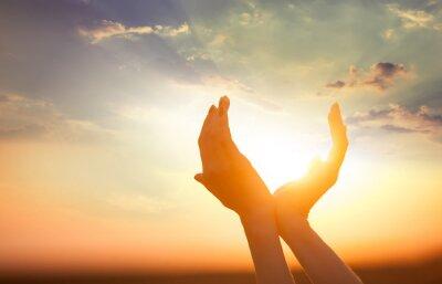 Cuadro manos que sostienen el sol al amanecer