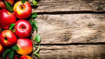 Cuadro Manzanas rojas frescas con hojas verdes en la mesa de madera.