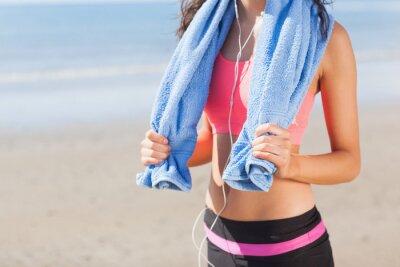 Cuadro Mediados de sección de la mujer sana con una toalla alrededor del cuello en la playa