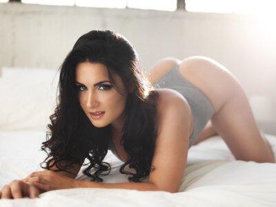 Cuadro Modelo sexy en la cama brillantemente iluminada en pose erótica