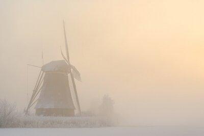 Molino de viento en un amanecer de invierno brumoso