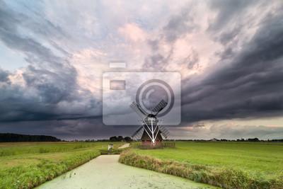Molino de viento holandés y cielo tempestuoso oscuro