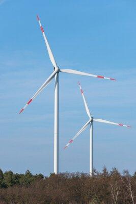 Molinos de viento detrás de un área de bosque
