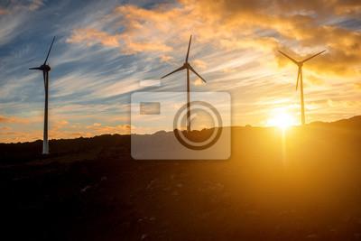 Molinos de viento eléctricos en el cielo de fondo en la puesta de sol