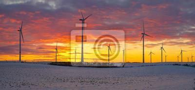 Molinos de viento (turbinas de viento) en el campo cubierto de nieve al atardecer