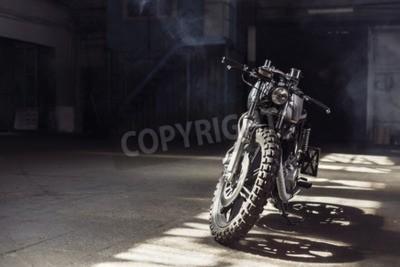 Cuadro Motocicleta de la vendimia que se coloca en un edificio oscuro en los rayos de la luz del sol. Colores tonificados. Vista frontal