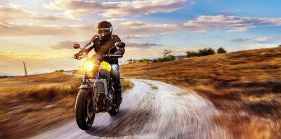 Cuadro Motorrad fährt auf freier Landstrasse en den Sonnenuntergang