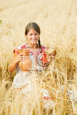 Muchacha con pan en el campo de cereales