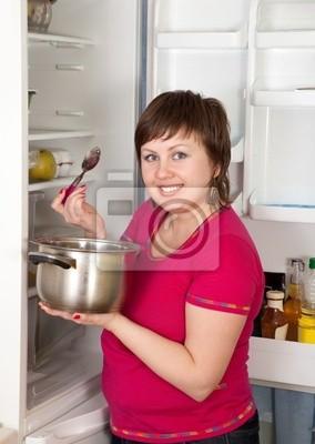 Mujer con la cacerola cerca del refrigerador