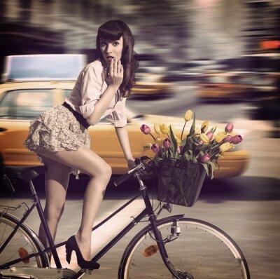 Cuadro Mujer de la vendimia en la bicicleta en una calle de la ciudad con los taxis