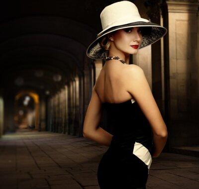 Cuadro Mujer en traje negro y sombrero blanco grande por sí solo al aire libre en la noche