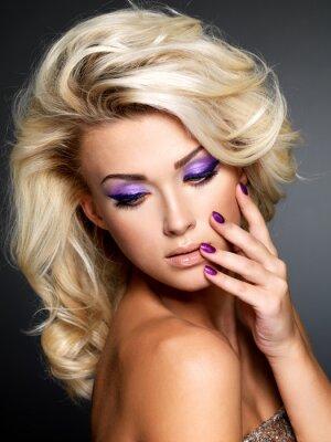 Cuadro Mujer hermosa con la belleza púrpura manicura y maquillaje de ojos.
