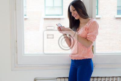 2c9b7f1ca8548 Mujer joven hermosa que usa su teléfono móvil en casa. pinturas para ...