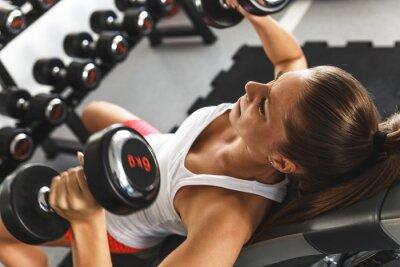 Cuadro Mujer levantando pesas y trabajar en el pecho en el gimnasio