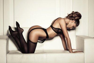 Cuadro mujer sexy en ropa interior negro seductora sentada en un sofá en sto