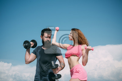 Cuadro Muscular and strong. Sexy woman and hipster having muscular build and physical fitness. Muscular couple doing muscle training with dumbbells. Fit girl and strong bearded man developing muscular power