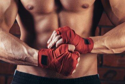 Cuadro Muscular Fighter con vendajes rojos contra el fondo de una pared de ladrillo