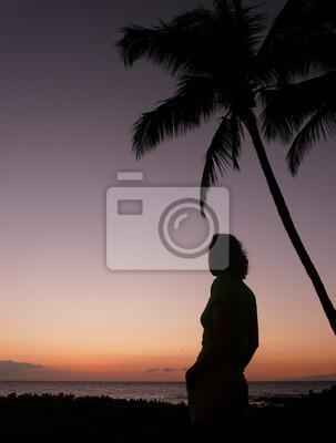 Niña silueteada bajo una palmera