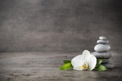 Cuadro Orquídeas y spa piedras blancas en el fondo gris.