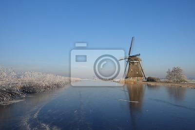 Paisaje invernal en Holanda con molino de viento y hielo.