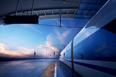 Cuadro parada del tren en la estación de tren, con la puesta de sol