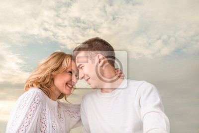 Pareja feliz sonriendo y mirando el uno al otro bajo el sk soleado