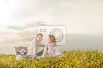 pareja sentada en un día de campo con cesta blanca bajo el cielo