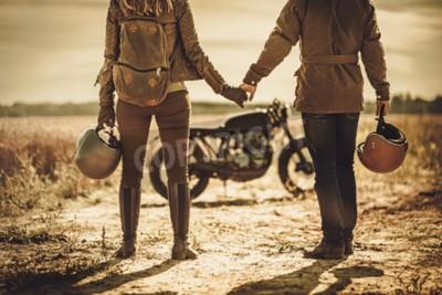 Cuadro Pares jovenes, elegantes del corredor del café en las motocicletas de encargo de la vendimia en un campo.